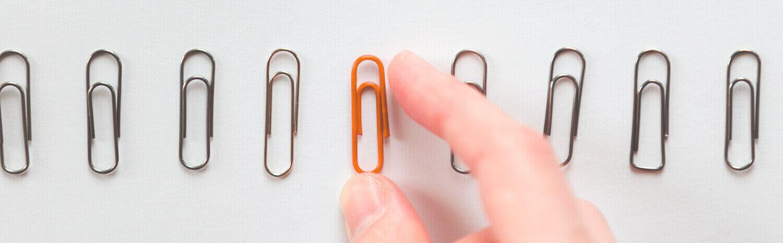 Foto de un clip naranja entre clips grises